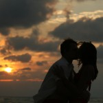 romantic couple kissing on the beach by sunset